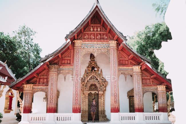 Woman standing at the door of beautiful temple in daylight. — Stock Photo