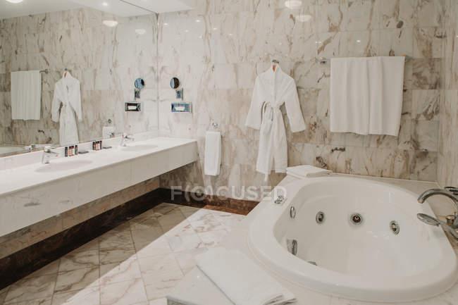 Interior view of luxury bathroom with big mirror and white bathrobe. — стоковое фото