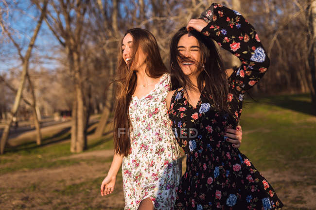 Two young girls walking in sunny woods together. — Stock Photo