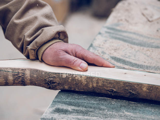 Crop hand of carpenter working with piece of wood on workbench — Stock Photo