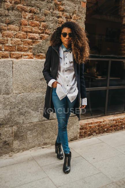 Mujer con estilo en gafas de sol posando en la pared de ladrillo - foto de stock