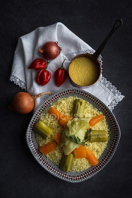 Directamente sobre la vista de cuscús con verduras en plato. - foto de stock