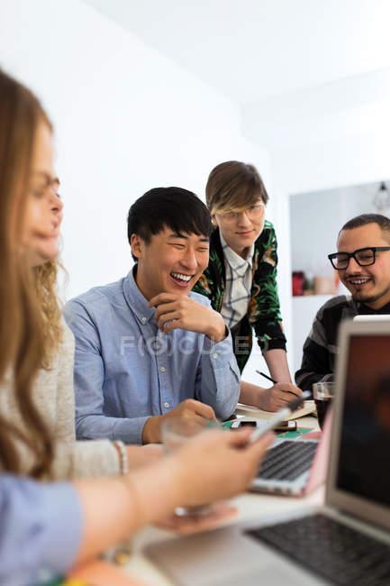 Gruppe von fröhlichen Kollegen mit Gadgets am Tisch sitzen — Stockfoto