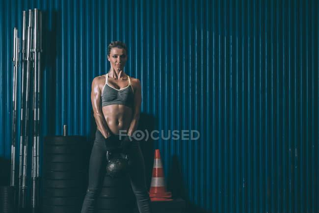 Подходящая женщина поднимает гири в спортзале и смотрит в камеру — стоковое фото