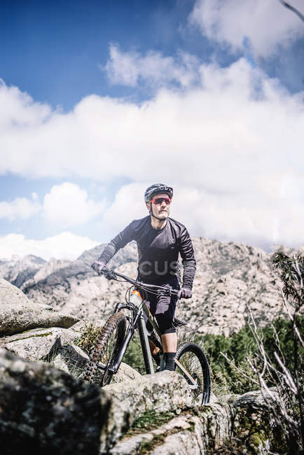 Mature biker riding bike at mountains on sunny day — Stock Photo