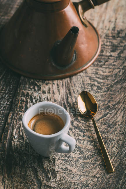 Coffee cup and spoon on rustic wooden table — Stock Photo