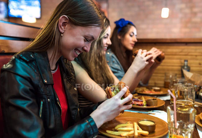 Cheerful young girls sitting together and eating burgers in restaurant. — Stock Photo
