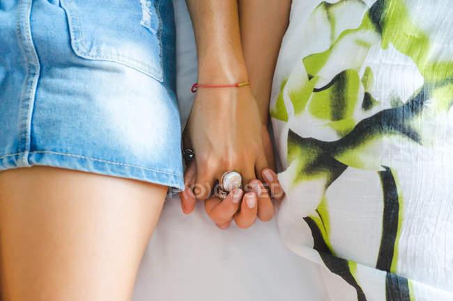 Abgeschnittenes Bild von Frauen, die Hände auf dem Bett halten — Stockfoto