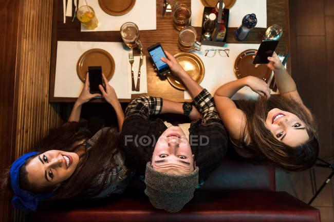 Amici allegri che sfogliano gli smartphone al tavolo del caffè e cercano la fotocamera — Foto stock
