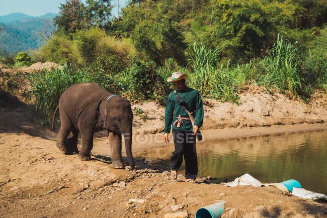 Chiang rai, thailand - 12. Februar 2018: asiatischer Mann mit Elefant am Ufer des Sees — Stockfoto