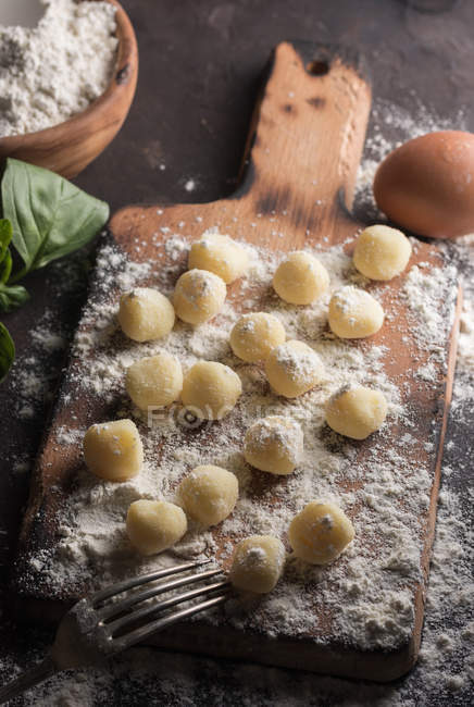 Raw gnocchi on wooden cutting board — Stock Photo