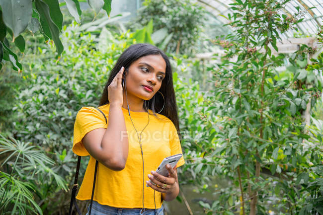 Young girl applying earphones by plants in hothouse. — Stock Photo