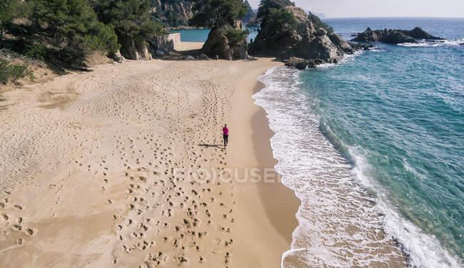 Пташиного польоту жінка працює на піщаному пляжі — стокове фото