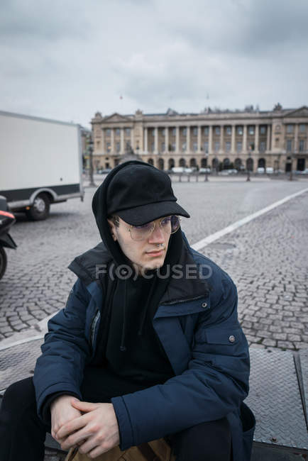 Pensive young in glasses and cap sitting at city square and looking away. — Stock Photo