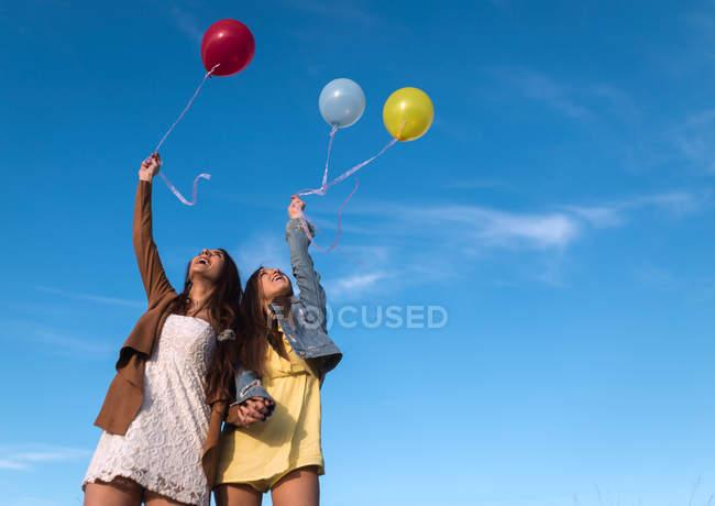 Junge Mädchen Hand in Hand mit Luftballons in der Natur zusammen — Stockfoto