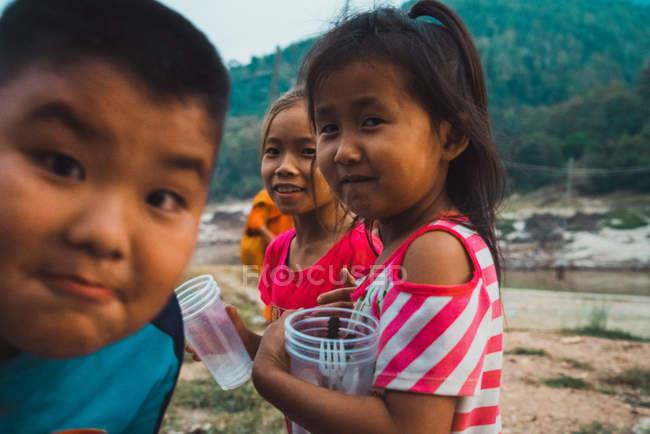 Лаос-Лютий 18, 2018: Веселої молоді діти з пластикового стакану в природі. — стокове фото