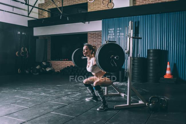 Fit femme blonde accroupie avec barre de poids dans la salle de gym — Photo de stock