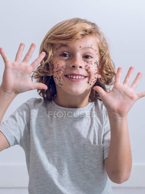 Веселый мальчик с конфетти на лице — стоковое фото