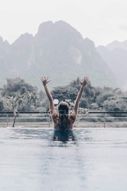 Vista posteriore della donna in piscina braccia tese fino su sfondo di montagne delle piogge tropicali — Foto stock