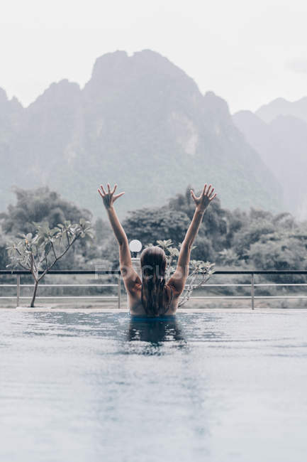 Rear view of woman in pool outstretching arms up on background of rainy tropical mountains — Stock Photo