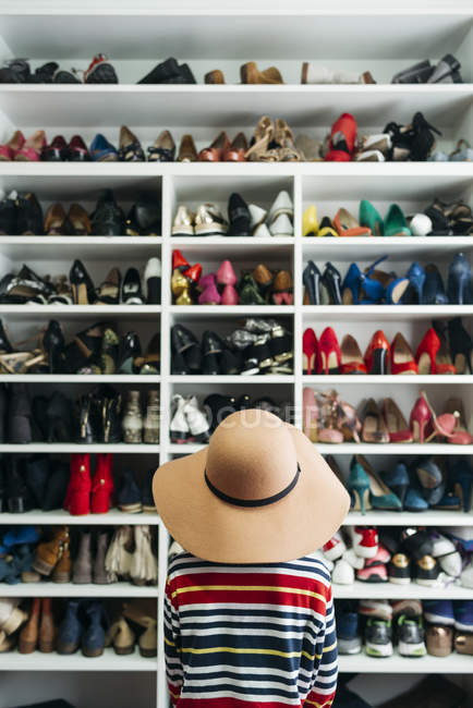 Rear view of woman sitting in front of shelves with different shoes — Stock Photo