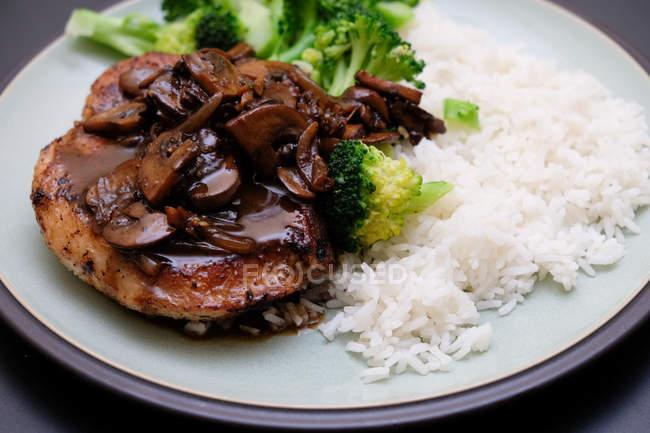 Кусок жареного вкусного мяса с соусом, подается с рисом и брокколи — стоковое фото