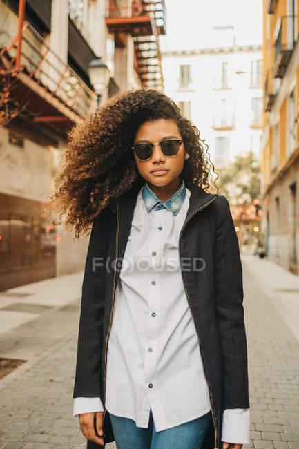 Stylish woman in sunglasses walking on street — Stock Photo