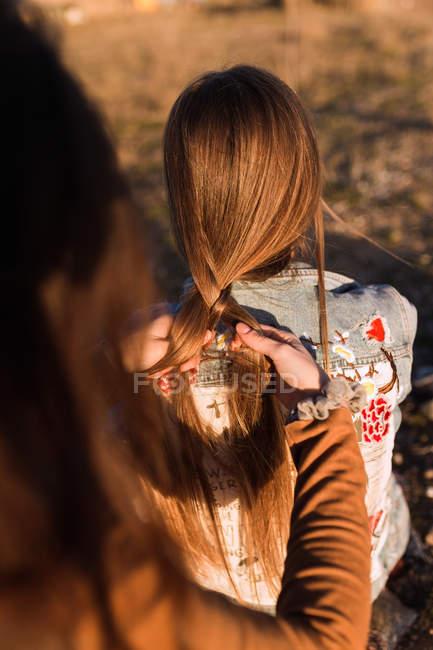Обтинання жінка плетіння з подругою в Сонячний природи — стокове фото