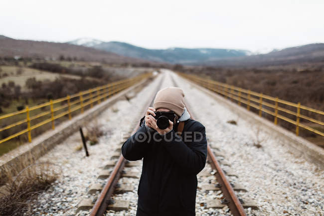 Front view of photographer aiming on railroad at nature — Stock Photo