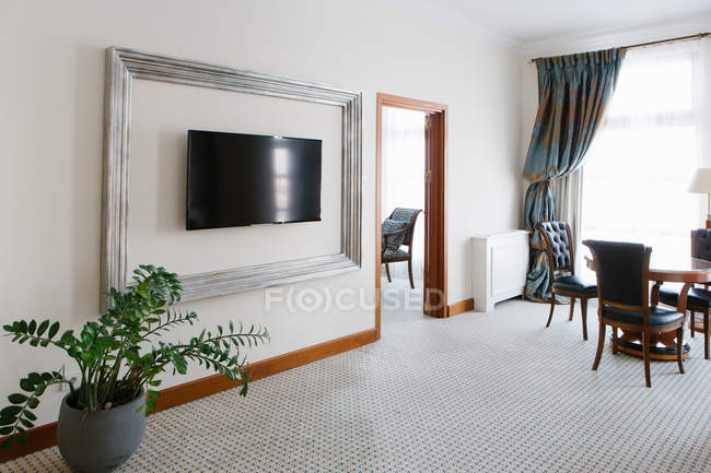 Interior of luxury hotel room with chairs and TV set hanging on wall. — Stockfoto