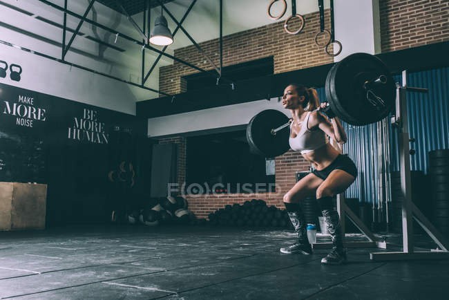 Side view of fit blonde woman lifting bar weights in gym hall — Stock Photo