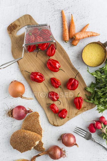 Directamente encima de la vista de pimientos rojos frescos y otros ingredientes en la mesa - foto de stock