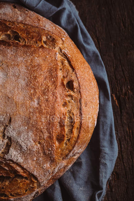 Rustic loaf of artisan bread on dark background — Stock Photo