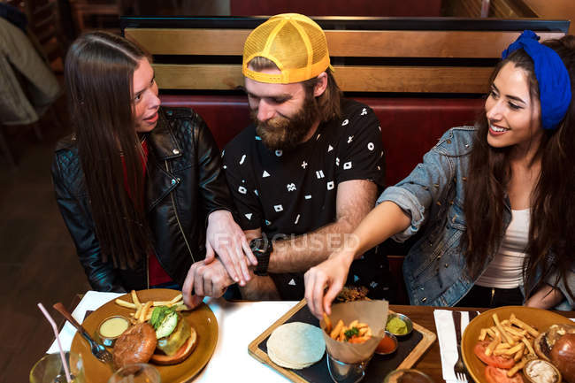 Веселые друзья дегустируют еду в ресторане . — стоковое фото