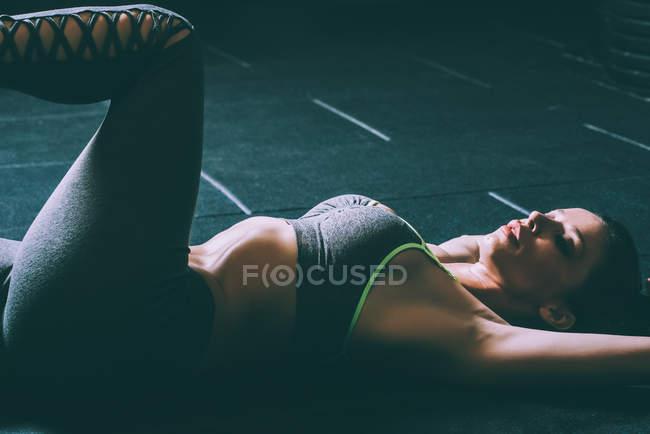 Forme femme blonde, couché sur le plancher qui s'étend et fait des craquements dans la salle de gym — Photo de stock