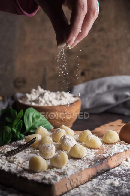 Crop female hand pouring flour on raw gnocchi at table — Stock Photo