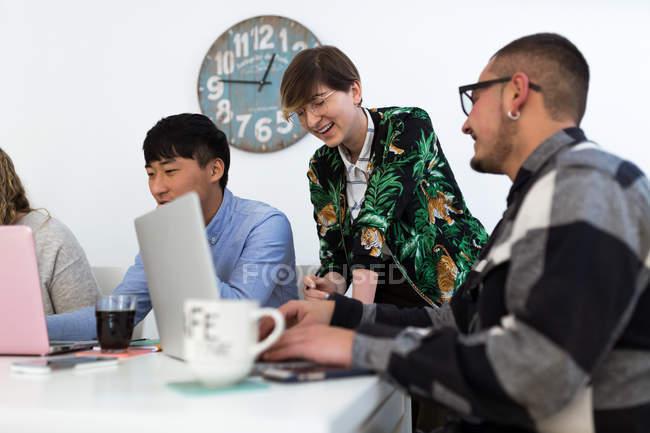 Mitarbeiter mit Gadgets am Tisch sitzen und lachen und Fröhlichkeit — Stockfoto