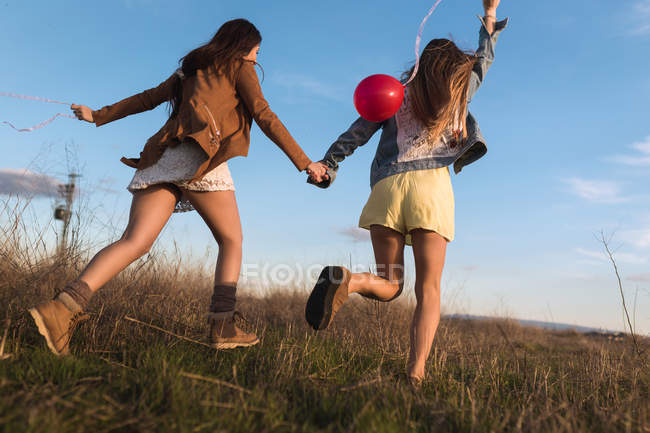 Young women holding hands and running with balloons at field — Stock Photo