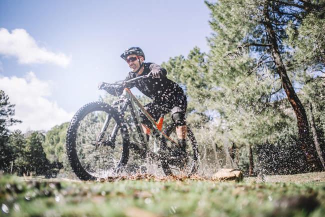 Ciclista madura salpicos de água com bicicleta de montanha em natureza — Fotografia de Stock