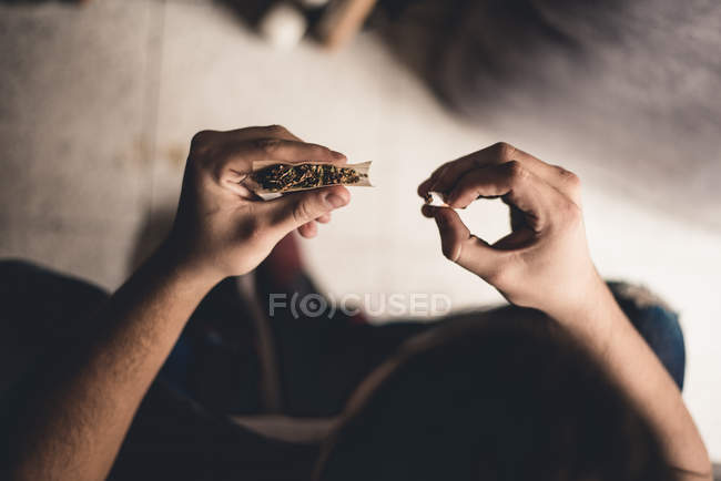 From above male hands purring tip in joint — Stock Photo