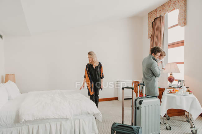 Familia feliz con niño y maletas en la habitación del hotel . - foto de stock