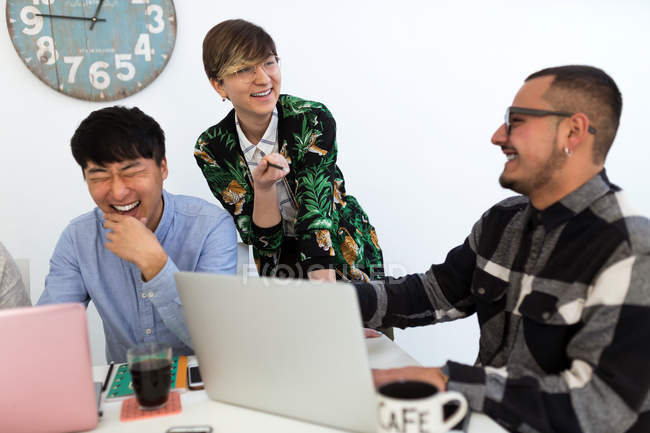 Laughing colleagues sitting with gadgets at meeting room — Stock Photo