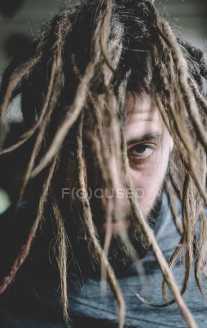 Homem, sacudindo o cabelo com dreadlocks e olhando para a câmera — Fotografia de Stock