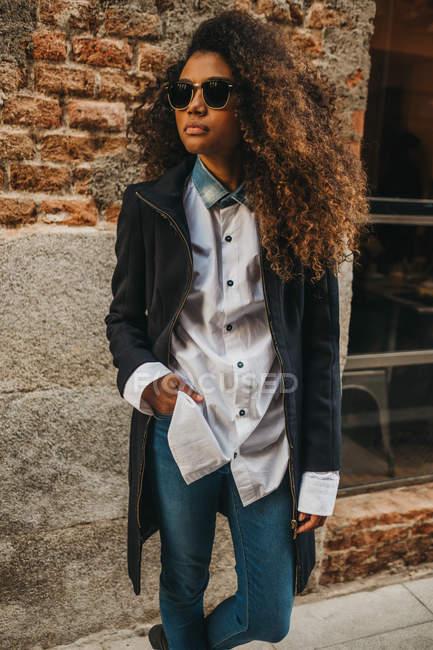 Stylish woman in sunglasses at brick wall — Stock Photo