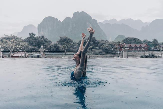 Vista lateral de la alegre mujer outstretching brazos para arriba en la piscina - foto de stock