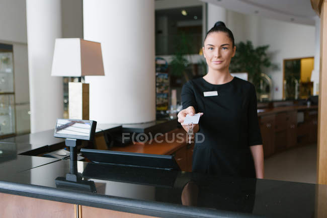 Hotel worker standing at reception and giving key — Stock Photo