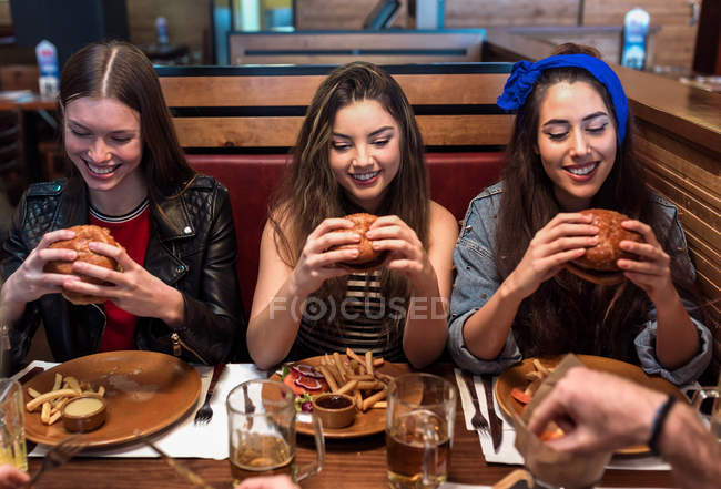 Smiling girls  sitting at cafe table and holding burgers — Stock Photo