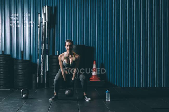 Forme femme blonde accroupie avec kettlebell en gym — Photo de stock