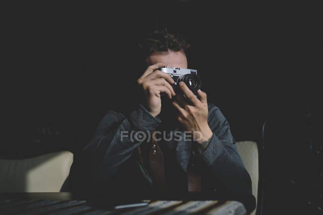 Homme photographe assis et visant avec appareil photo — Photo de stock