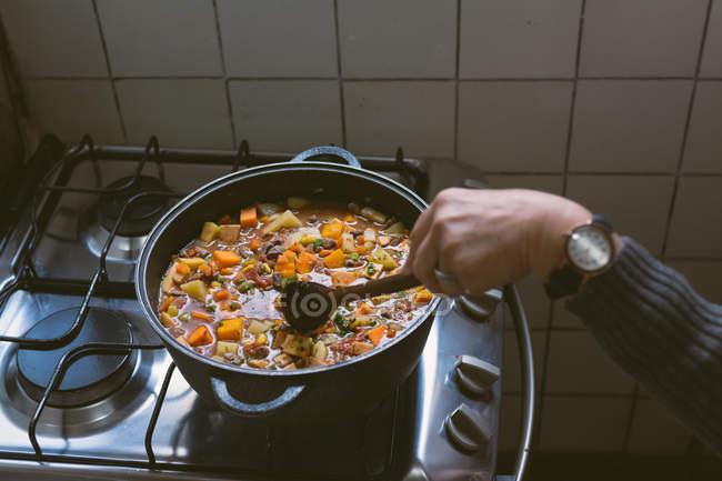 Mão feminina de colheita com relógio de mão mexendo de carne cozido em panela no fogão — Fotografia de Stock